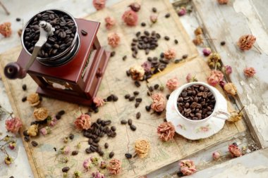 Coffee beans and dried roses scattered upon the old map
