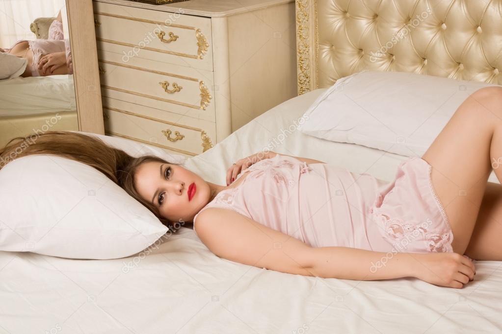 Donna giovane attraente emotiva sessuale sdraiato sul letto in ...