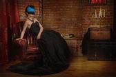 Sinnliche gotische Frau in einem langen wunderschönen schwarzen Kleid und Maske