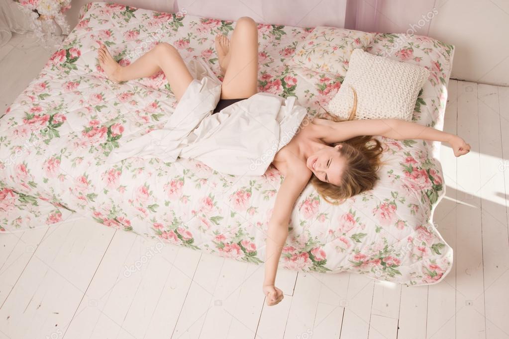 Giovane donna attraente sessuale sdraiato sul letto in camera da ...