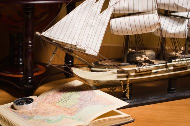 model sailing ship, map book and compass