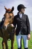 Fotografie schöne junge Jockeyspielerin mit ihrem Pferd