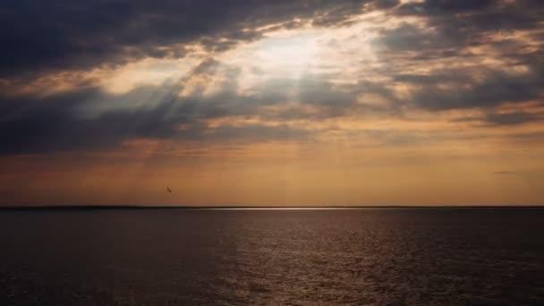 Timelapse krásný západ slunce s sluneční paprsky koryta mraky nad mořem