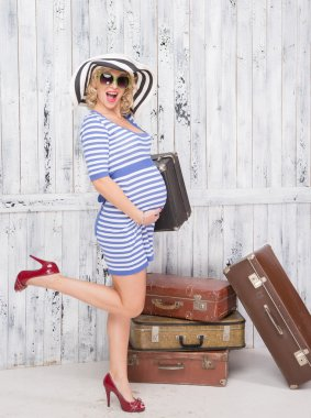 Pregnant tourist with suitcases