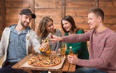 Happy friends resting in pizzeria