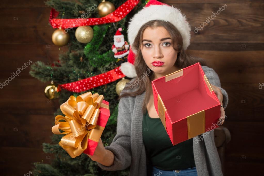 Beautiful girl demonstrating empty box of present near New Year tree