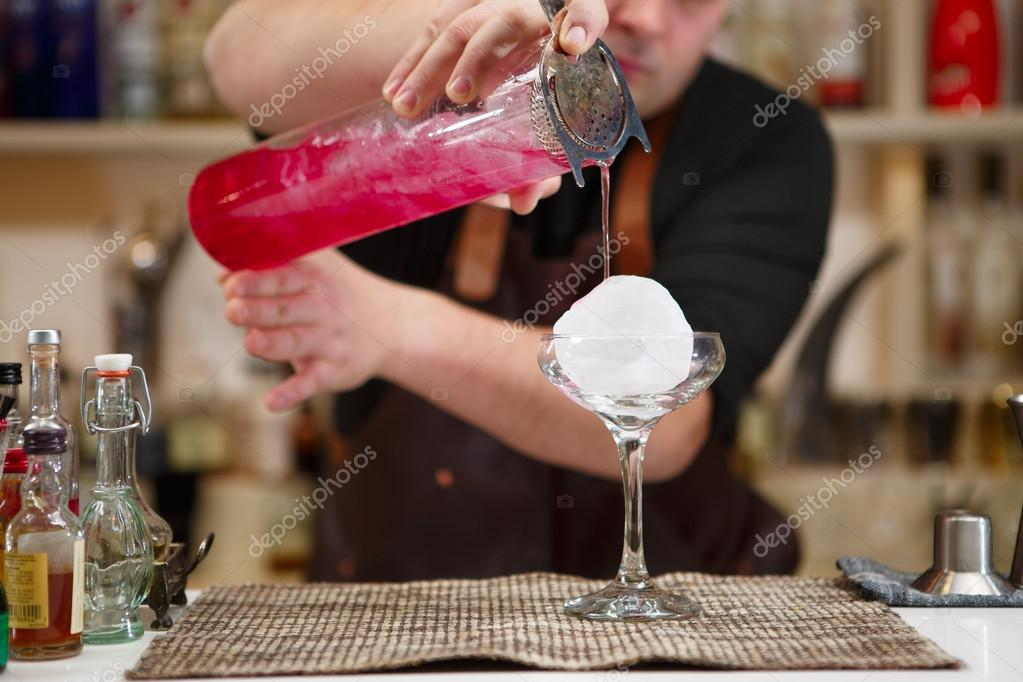 barman pouring a pink cocktail drink
