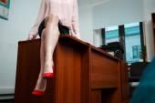 Sexy moderátorka sedí na stole v kanceláři