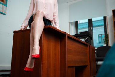 Sexy businesswoman sitting on table at office.