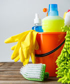 Fotografie Bucket with cleaning items on light background