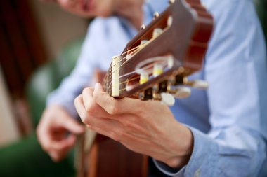 Young musician playing at acoustic guitar