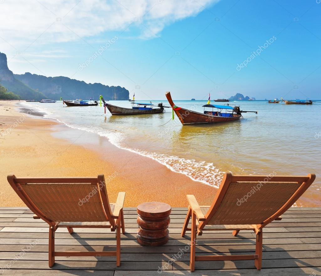 Two wooden chaise lounges and  native boats