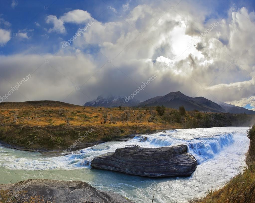 The cascading waterfall and  billowing clouds