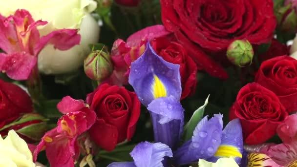 Kapky vody dopadající na krásnou kytici růží, iris a kosatců.