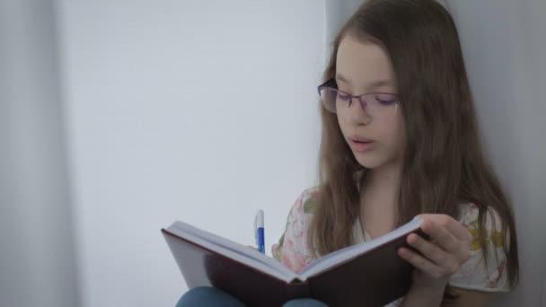 Gyönyörű kicsi lány szemüveg szorgalmasan csinál a házi feladatot, ablak.
