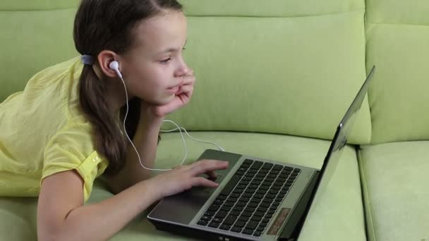 Beautiful little girl lying on the couch and watching movie on laptop.