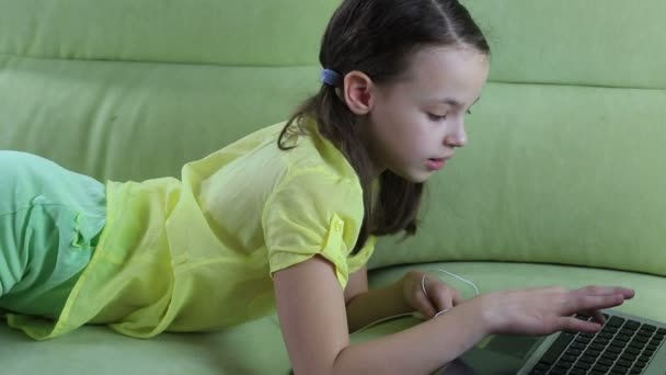 Beautiful little girl puts headset and typing on laptop.