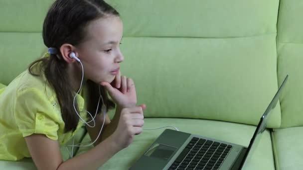 Frightened little girl looks terrible video on laptop.