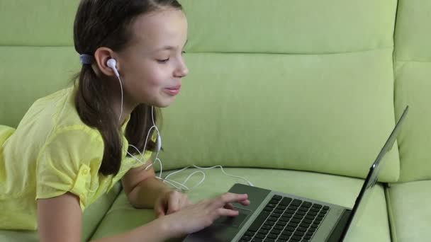 Emotional little girl talking on Skype at laptop.