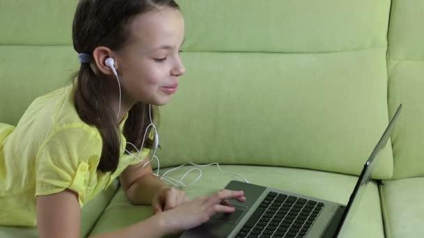 Emotional little girl talking on Skype at laptop.