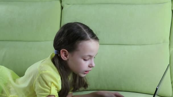 Beautiful little girl talking and typing on laptop.