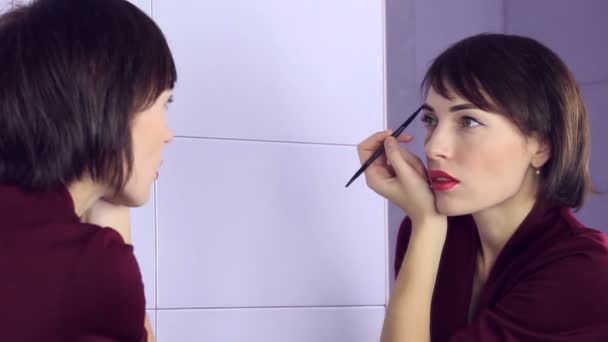 Beauty woman applying makeup. Beautiful girl looking in mirror and paints eyebrows brush.