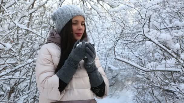 Krásná šťastná dívka prohřívá s horkým čajem. Zasněžené stromy v zimě parku.