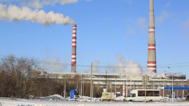 Wärmekraftwerk an sonnigen kalten Tagen. Industrierauch aus den Rohren gegen blauen Himmel.