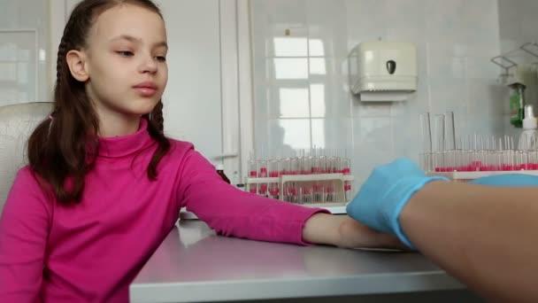 Sestra bere krev z prstu dítěte v lékařské laboratoři