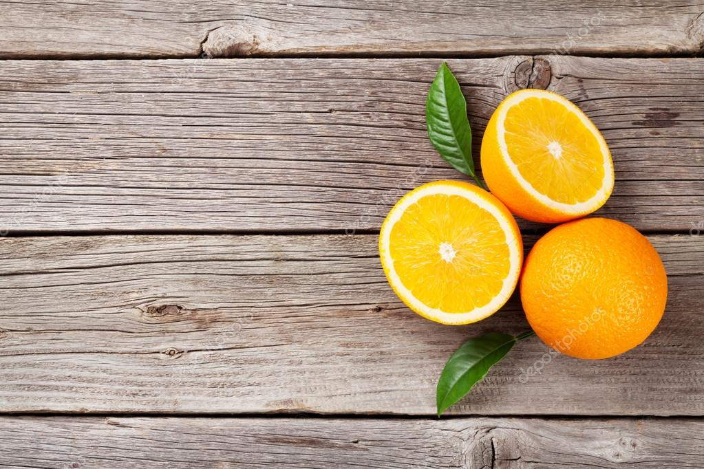 Fresh oranges on wooden table