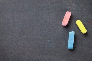 Colorful chalks on blackboard background