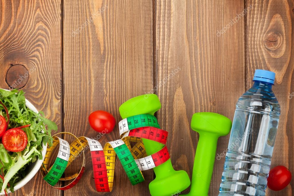 Dumbbells, tape measure and healthy food.