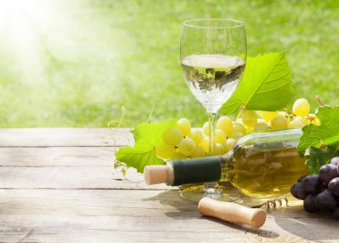 White wine glass and bottle with bunch of grapes