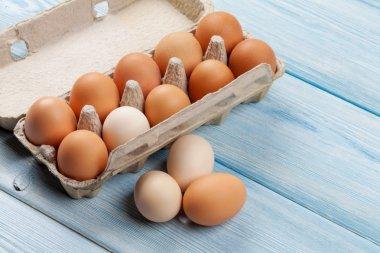 Cardboard egg box on blue wooden table stock vector