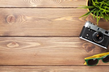 Camera, sunglasses and flower on office wooden desk table. Top view with copy space stock vector
