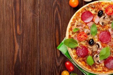 Italian pizza with pepperoni, tomatoes, olives and basil on wooden table. Top view with copy space stock vector