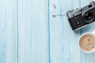 Travel camera and coffee cup on wooden table. Top view with copy space stock vector