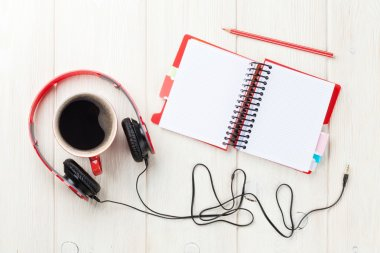 Headphones, coffee cup and notepad on desk