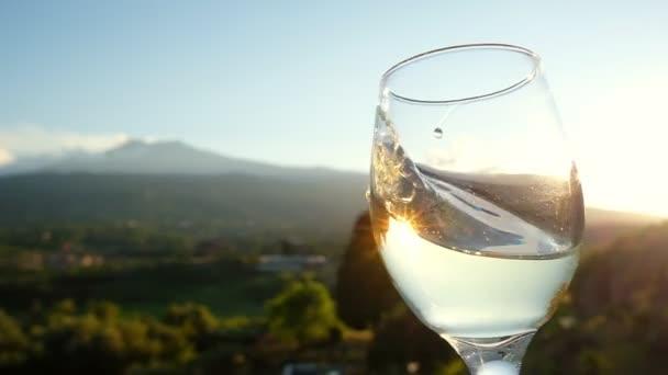 Sommelier mává mladým bílým vínem ve sklenici ve zpomaleném filmu.