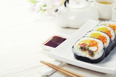Sushi set, green tea and sakura branch