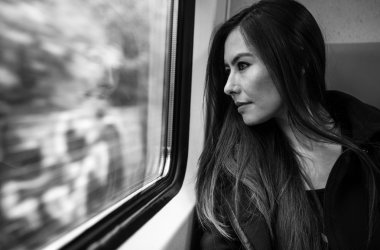 Portrait of beautiful young woman with long hairs looks out of train window.
