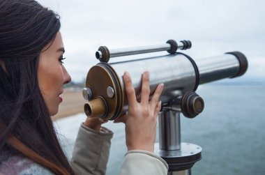 Beautiful young woman with magnificent hairs near telescope on pier in the Hague.