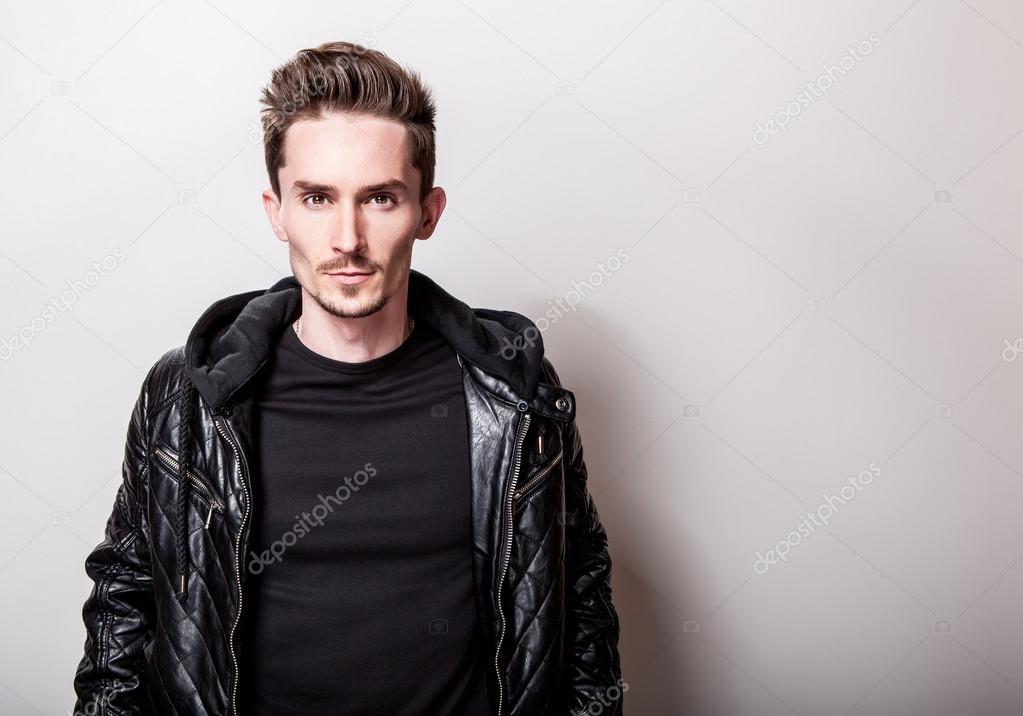 Uomo elegante attraente in giacca di pelle nera elegante in posa su sfondo  grigio chiaro — 8e6151ef039