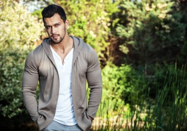 Sporty handsome man in casual clothes poses outdoor