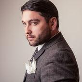 Elegantní mladý pohledný muž v šedém kostýmu. Portrét módní Studio
