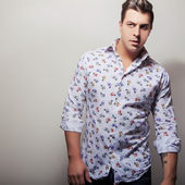 Elegant young handsome man in bright colorful shirt. Studio fashion portrait.