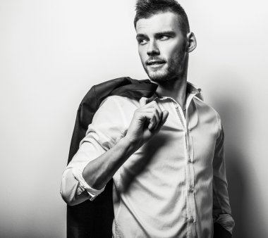 Elegant young handsome serious man in white shirt. Black-white studio fashion portrait.