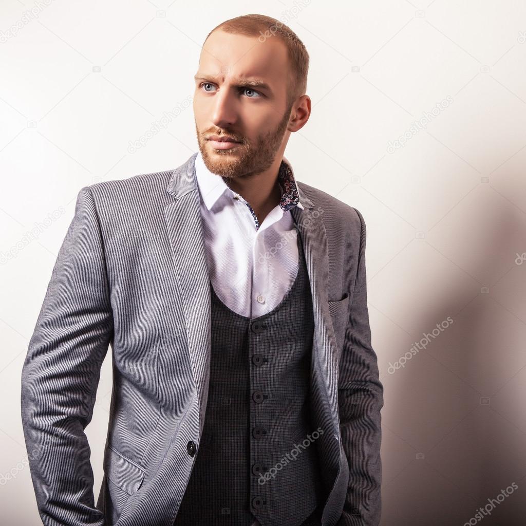5000f14307 Elegante giovane uomo bello in costume grigio. Ritratto dello studio ...