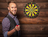 Fotografie Portrait of young friendly lucky man against old wooden wall with darts game. Concept: Hit in purpose. Photo.