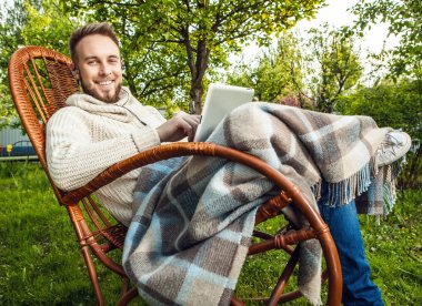 Friendly man sits in a rocking-chair with plaid & tablet in summer country garden.